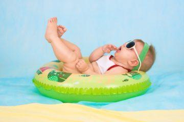 Kind mit Sonnenbrille in Babywanne