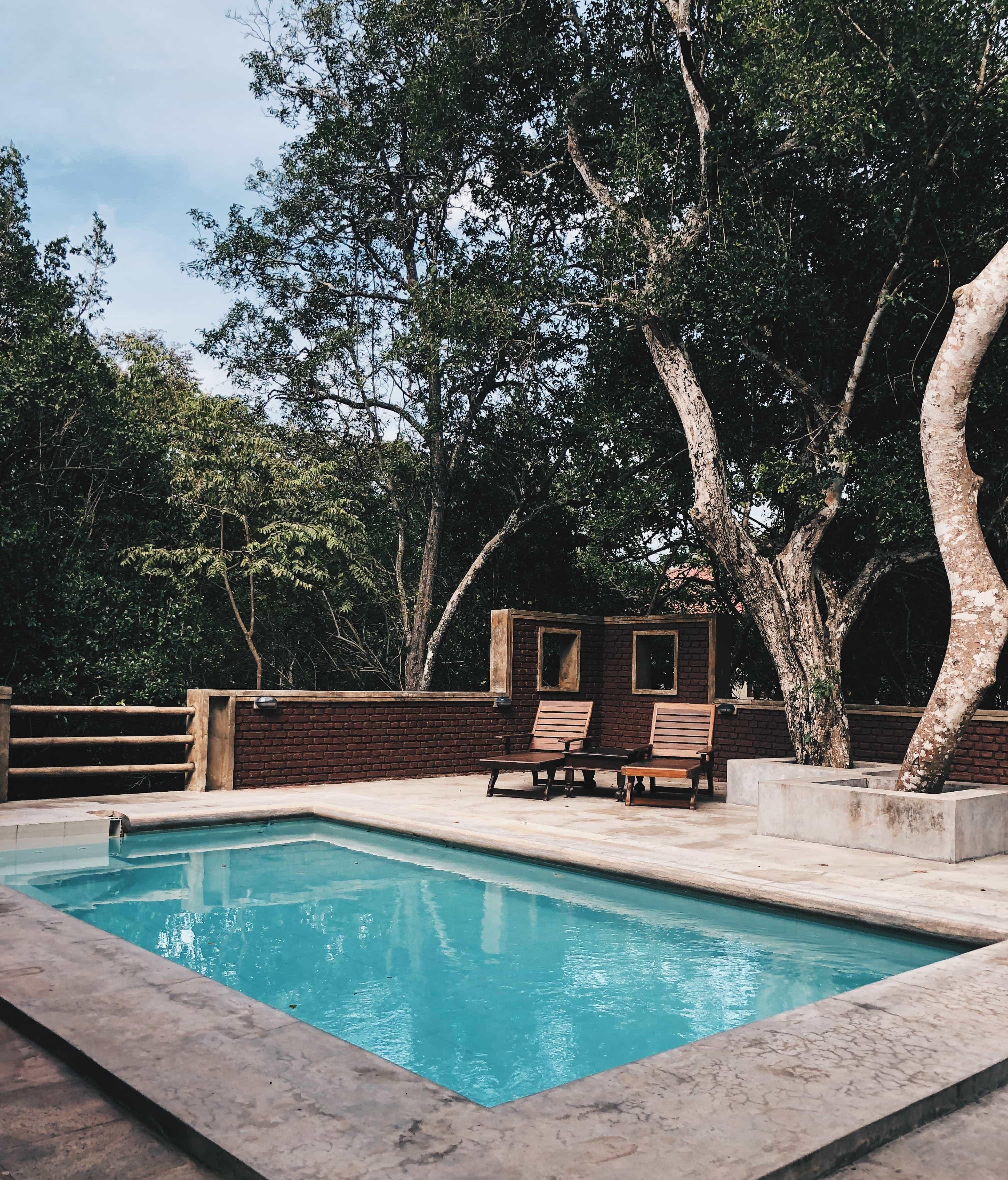 Eckiger Swimming Pool im Garten mit zwei Liegen