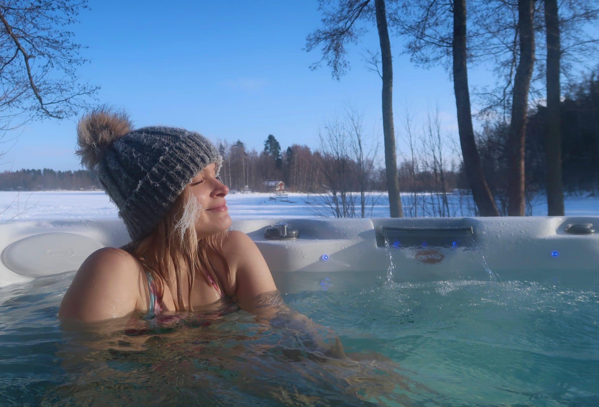 Frau mit Mütze in einem Whirlpool Outdoor im Winter